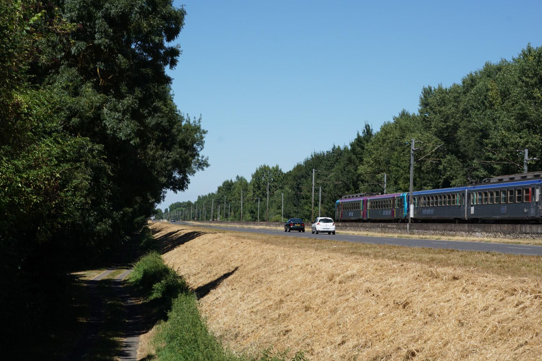 Links unten (z. T. im Schatten) der Radweg (schlechte Qualität), oben die Straße und die Eisenbahn
