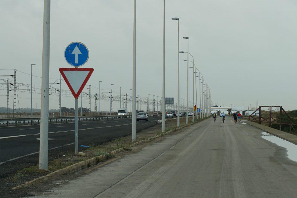 Eisenbahngleise, Straße, Radweg, rechts und links Wasser